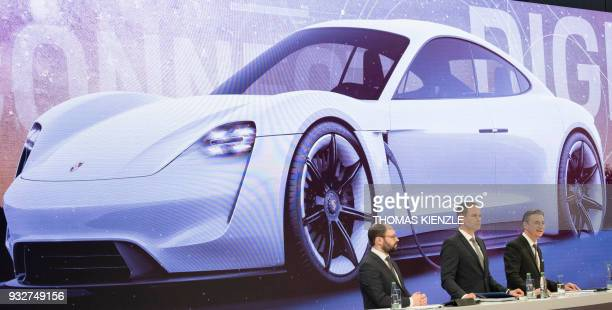 Oliver Blume CEO of German luxury carmaker Porsche AG CFO Lutz Meschke and spokesman Josef Arweck stand in front of a projection of a Porsche Mission...