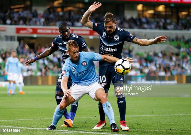 Oliver Bozanic of Melbourne City contests the ball with James Troisi of the Victory and Leroy George of the Victory during the round 22 ALeague match...