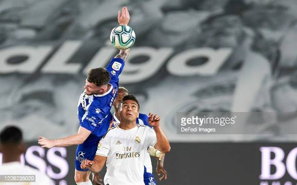 Oliver Burke of Deportivo Alaves and Carlos H. Casemiro of Real Madrid battle for the ball during the Liga match between Real Madrid CF and Deportivo...