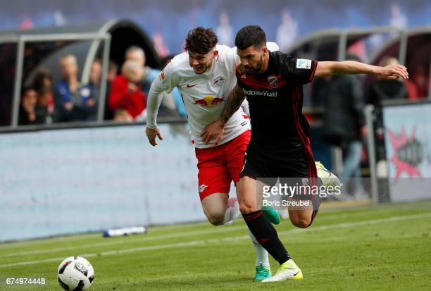 Oliver Burke of RB Leipzig is challenged by Anthony Jung of FC Ingolstadt 04 during the Bundesliga match between RB Leipzig and FC Ingolstadt 04 at...
