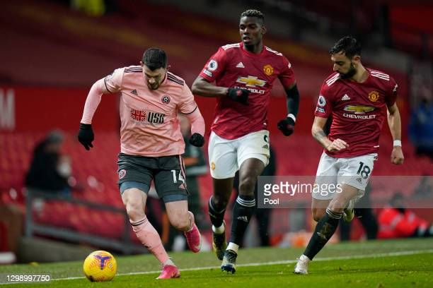 Oliver Burke of Sheffield United runs with the ball whilst under pressure from Paul Pogba and Bruno Fernandes of Manchester United during the Premier...