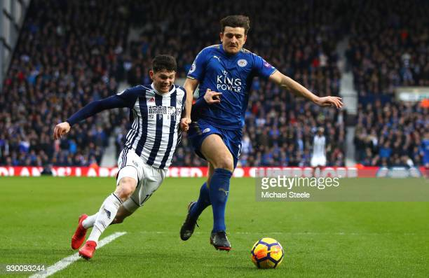 Oliver Burke of West Bromwich Albion is challenged by Harry Maguire of Leicester City during the Premier League match between West Bromwich Albion...