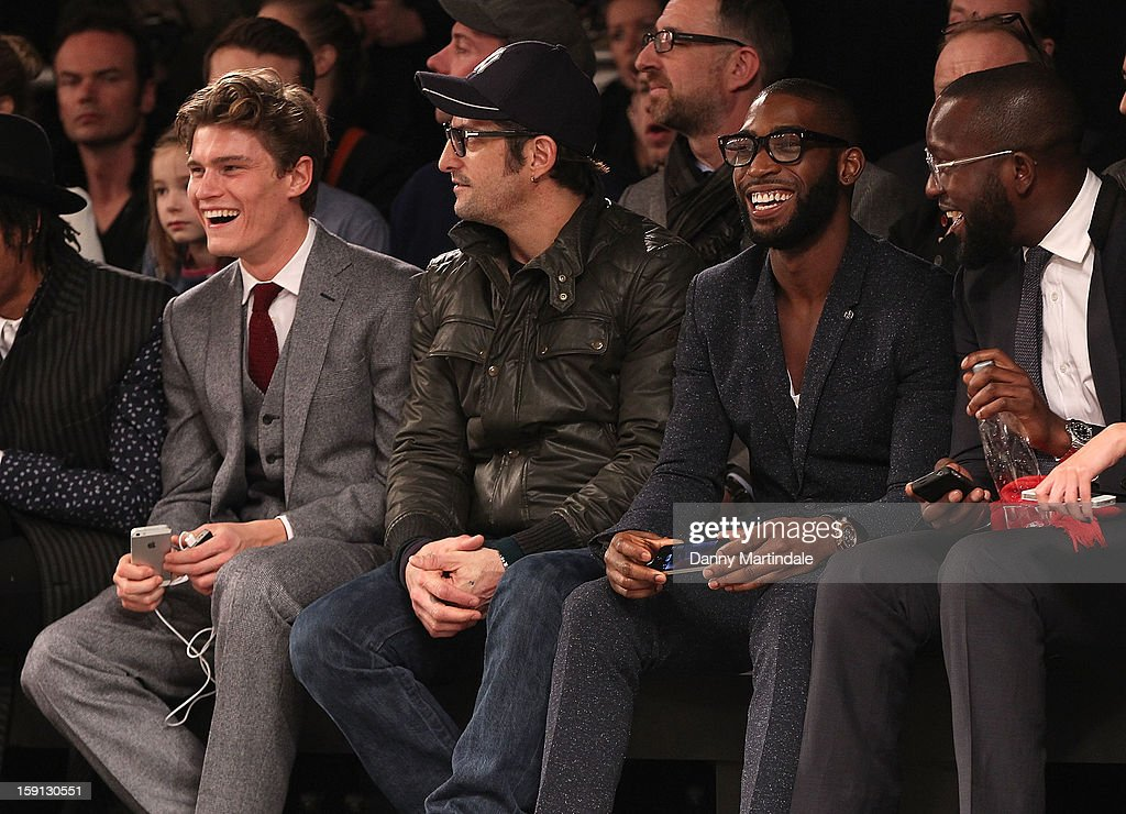 Oliver Cheshire (L) and Tinie Tempah (R) share a joke at the Oliver Spencer show at the London Collections: MEN AW13 at The Old Sorting Office on January 8, 2013 in London, England.