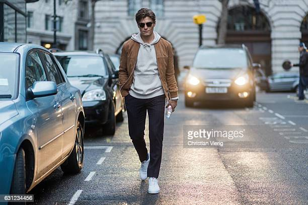 Oliver Cheshire wearing a grey hoody Ray Ban sunglasses brown jacket during London Fashion Week Men's January 2017 collections at KTZ on January 8...