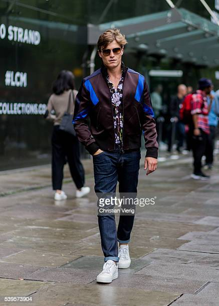 Oliver Cheshire wearing a sports jacket floral printed shirt and navy denim jeans outside Christopher Raeburn during The London Collections Men SS17...