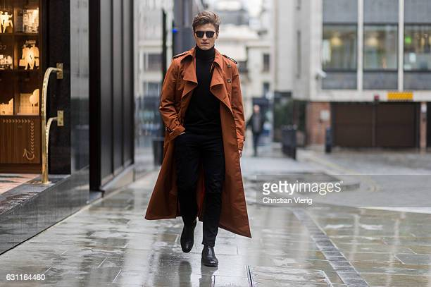 Oliver Cheshire wearing an orange brown coat black turtleneck sweater black pants black boots during London Fashion Week Men's January 2017...