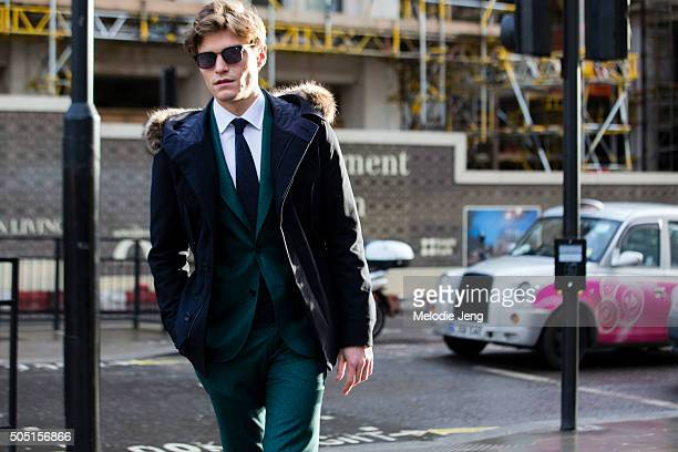 Oliver Cheshire wears Dita sunglasses a furlined blue parka and a green Hardy Amies suit during The London Collections Men AW16 at The Strand on...