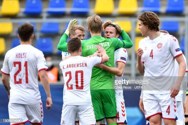 Oliver Christensen of Denmark celebrates with team mate Morten Hjulmand after saving a penalty taken by Sveinn Aron Gudjohnsen of Iceland during the...