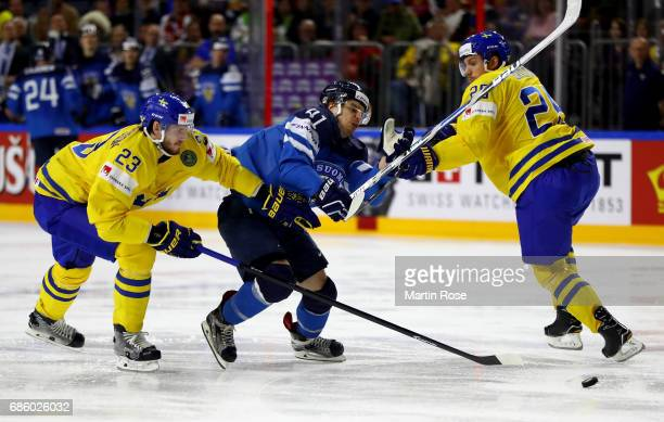 Oliver Ekman Larsson and Jonas Brodin of Sweden challenge Antti Pihlstrom of Finland for the puck during the 2017 IIHF Ice Hockey World Championship...