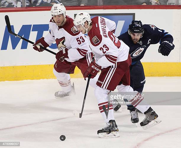 Oliver Ekman-Larsson and Derek Morris of the Phoenix Coyotes skate the puck against Andrew Ladd of the Winnipeg Jets in first period action in an NHL...