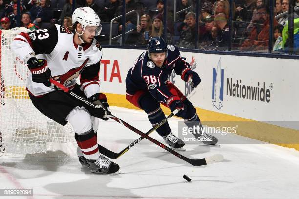 Oliver EkmanLarsson of the Arizona Coyotes and Boone Jenner of the Columbus Blue Jackets battle for control of the puck during the first period on...