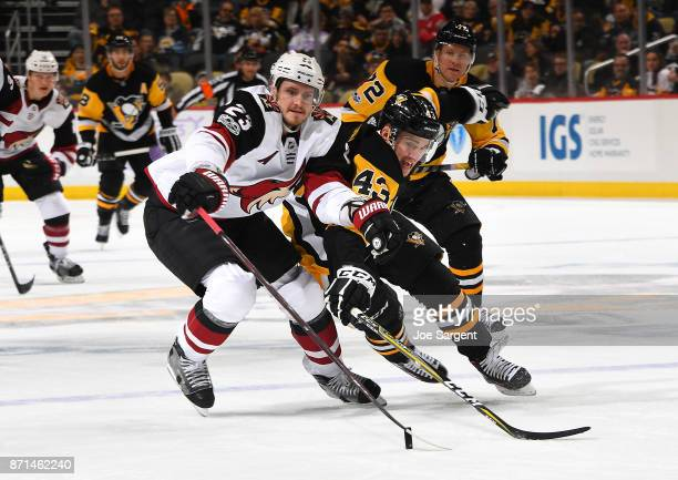 Oliver EkmanLarsson of the Arizona Coyotes and Conor Sheary of the Pittsburgh Penguins battle for the loose puck at PPG Paints Arena on November 7...