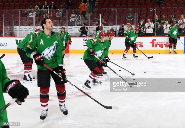 Oliver EkmanLarsson of the Arizona Coyotes and his teammates wear special green warm up jersey in recognition of St Patrick's Day prior to a game...