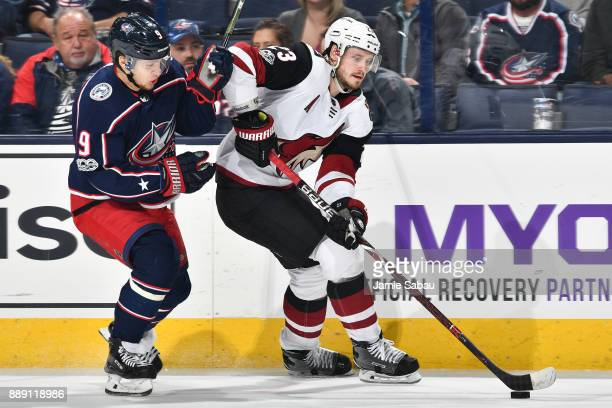 Oliver EkmanLarsson of the Arizona Coyotes attempts to skate the puck away from Artemi Panarin of the Columbus Blue Jackets during the third period...
