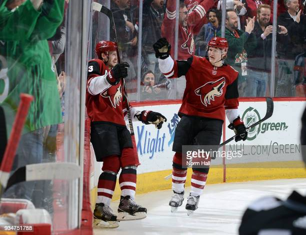 Oliver EkmanLarsson of the Arizona Coyotes celebrates with teammate Christian Dvorak after scoring a goal against the Calgary Flames during the third...