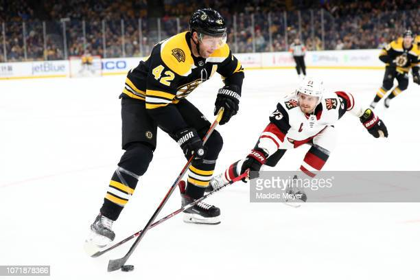 Oliver EkmanLarsson of the Arizona Coyotes defends David Backes of the Boston Bruins during the first period at TD Garden on December 11 2018 in...