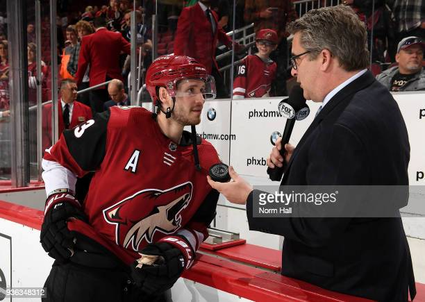 Oliver EkmanLarsson of the Arizona Coyotes is given his 100th career NHL goal puck by Fox Sports West announcer Todd Walsh after a game against the...