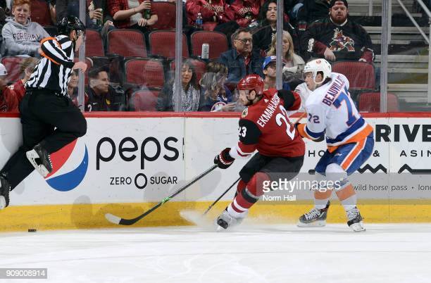 Oliver EkmanLarsson of the Arizona Coyotes passes the puck along the boards away from Anthony Beauvillier of the New York Islanders during the third...