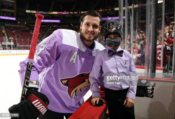 Oliver EkmanLarsson of the Arizona Coyotes poses with honorary captain seven year old Bruce ClarkFrye who is battling leukenia before the start of a...