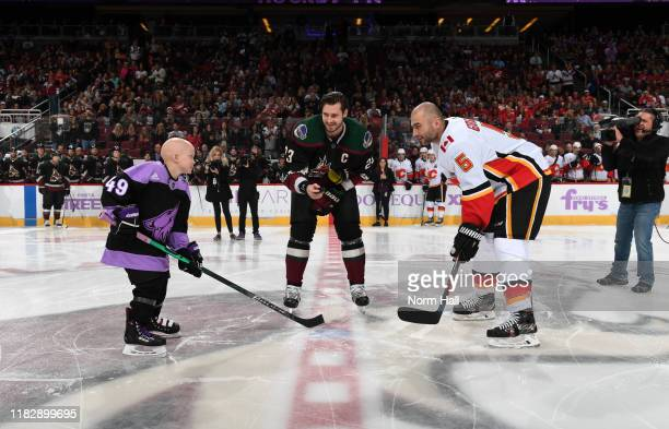 Oliver EkmanLarsson of the Arizona Coyotes prepares to drop the ceremonial puck between Mark Giordano of the Calgary Flames and eightyear old...