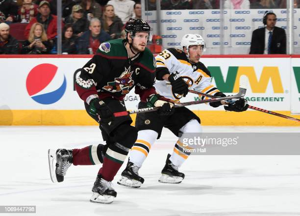 Oliver EkmanLarsson of the Arizona Coyotes skates up ice along side of Brad Marchand of the Boston Bruins at Gila River Arena on November 17 2018 in...
