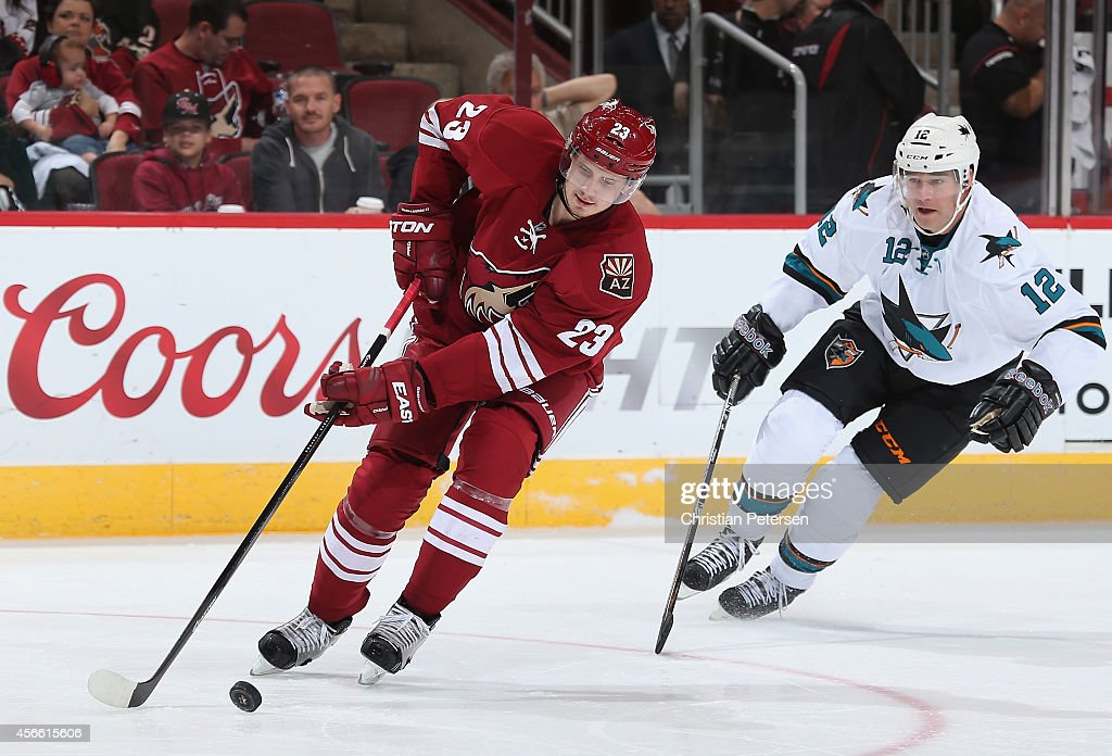 Oliver Ekman-Larsson #23 of the Arizona Coyotes skates with the puck ahead of Patrick Marleau #12 of the San Jose Sharks during the third period of the preseason NHL game at Gila River Arena on October 3, 2014 in Glendale, Arizona. The Sharks defeated the Coyotes 3-1.