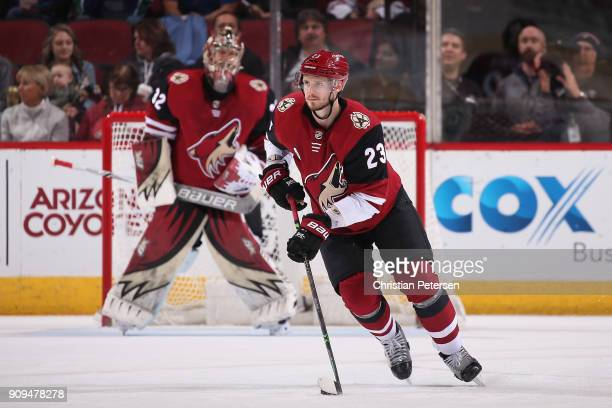 Oliver EkmanLarsson of the Arizona Coyotes skates with the puck ahead of goaltender Antti Raanta during the NHL game against the New York Islanders...