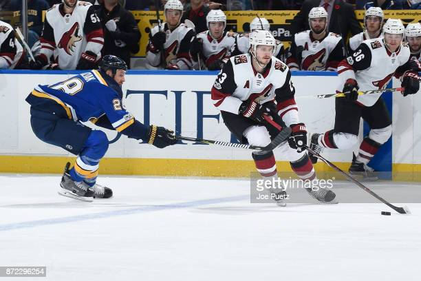 Oliver EkmanLarsson of the Arizona Coyotes skates with the puck as Kyle Brodziak of the St Louis Blues adds pressure at Scottrade Center on November...