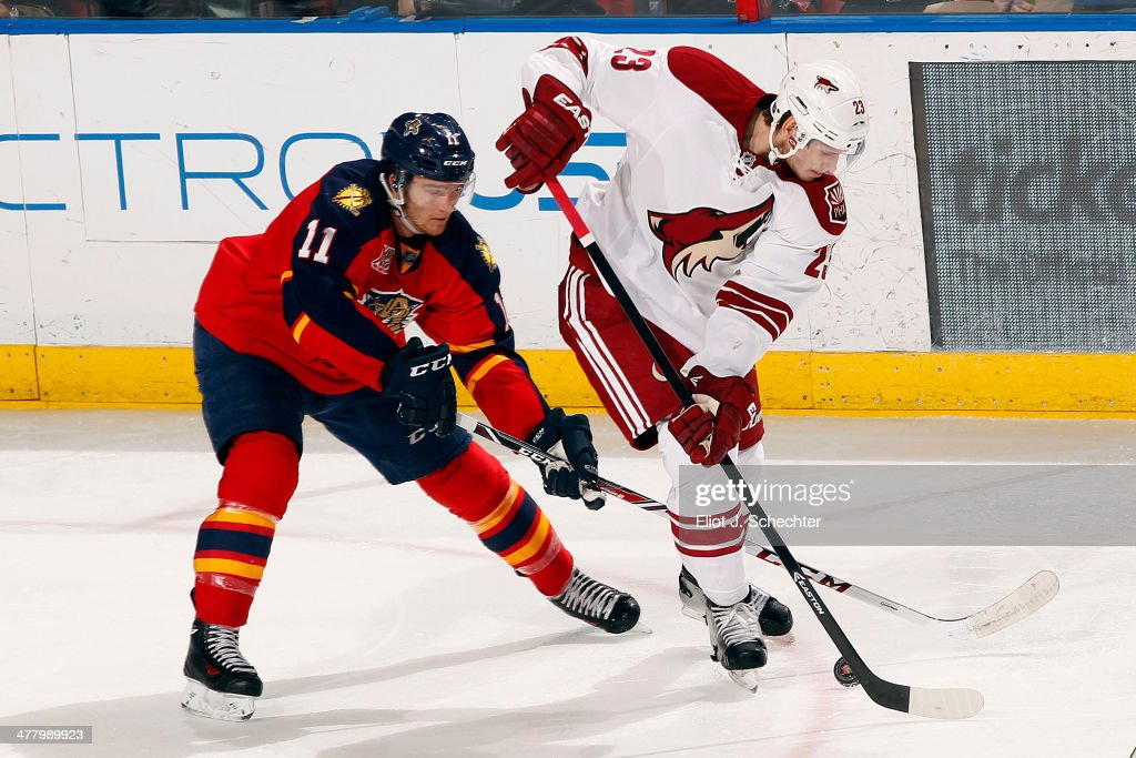 Oliver Ekman-Larsson #23 of the Phoenix Coyotes crosses sticks with Jonathan Huberdeau #11 of the Florida Panthers at the BB&T Center on March 11, 2014 in Sunrise, Florida.