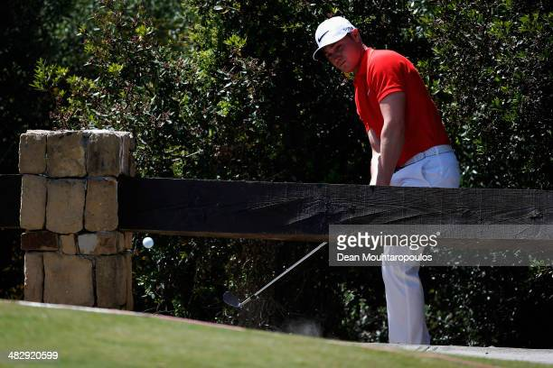 Oliver Fisher of England hits his third shot on the 1st hole from behind the wood fence during day three of the NH Collection Open held at La Reserva...