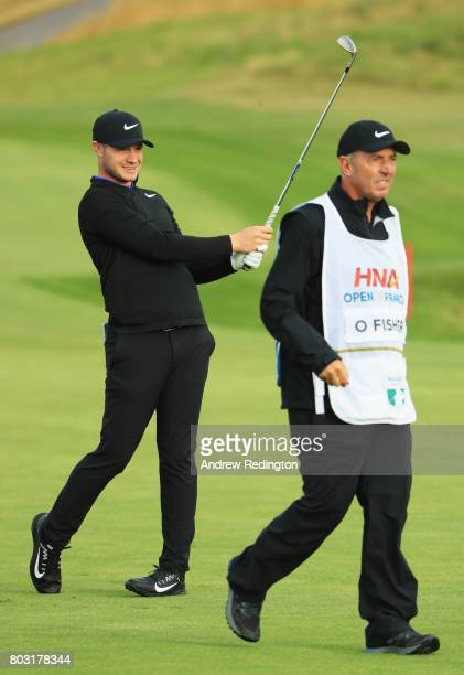 Oliver Fisher of England plays his second shot on the 10th hole with caddie Phil 'Wobbly' Morbey during day one of the HNA Open de France at Le Golf...