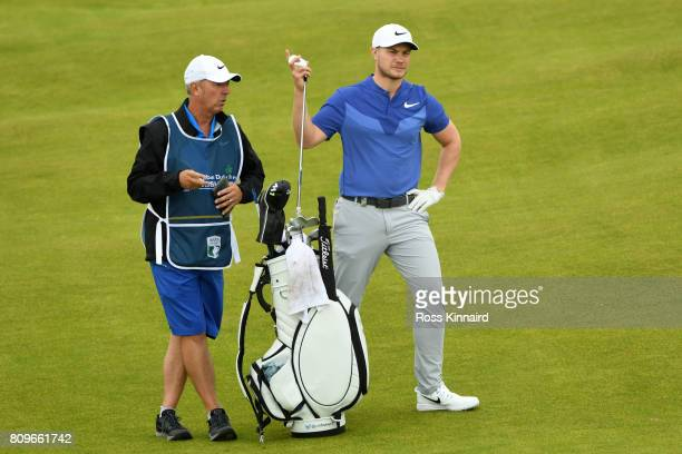 Oliver Fisher of England prepares to hit his second shot on the 14th hole with caddie Phil Morbey during day one of the Dubai Duty Free Irish Open at...