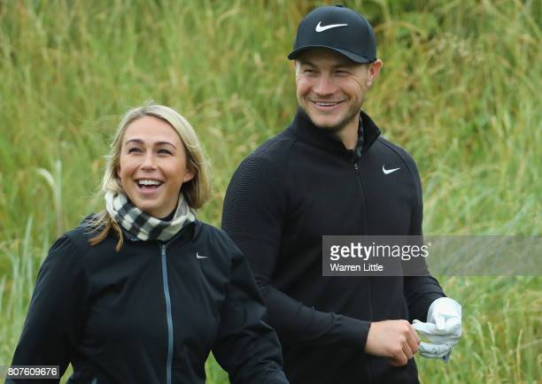 Oliver Fisher of England walks with his girlfriend Paige Louise Willis during previews ahead of the Dubai Duty Free Irish Open at Portstewart Golf...