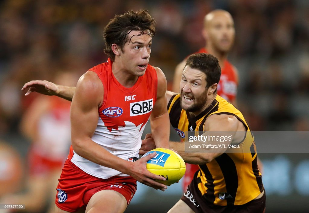 Oliver Florent of the Swans in action ahead of James Frawley of the Hawks during the 2018 AFL round eight match between the Hawthorn Hawks and the Sydney Swans at the Melbourne Cricket Ground on May 11, 2018 in Melbourne, Australia.