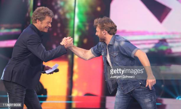 Oliver Geissen shakes hands with Nick Ferretti during the second event show of the tv competition Deutschland sucht den Superstar at Coloneum on...
