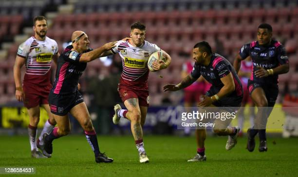 Oliver Gildart of Wigan gets past Danny Houghton and Ligi Sao of Hull FC during the Betfred Super League Play-Off Semi-Final between Wigan Warriors...