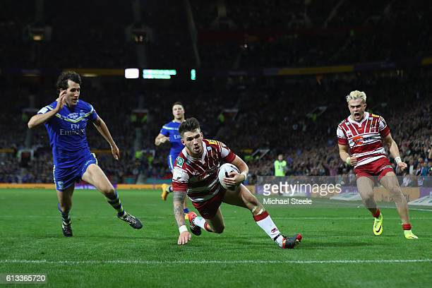 Oliver Gildart of Wigan scores his sides opening try despite the attention of Stefan Ratchford of Warrington during the First Utility Super League...