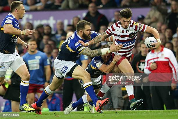 Oliver Gildart of Wigan Warriors is tackled by Rob Burrow and Adam Cuthertson of Leeds Rhinos during the First Utility Super League Grand Final...