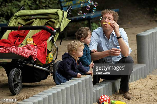 Oliver H a married federal employee on 6month paternity leave blows soap bubbles for his twin 14monthold daughters Lotte and Alma at a playground on...