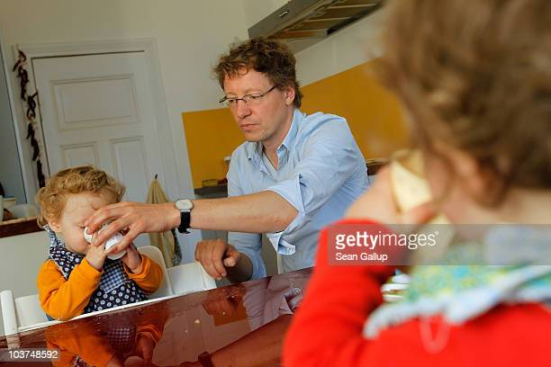 Oliver H. A married federal employee on 6-month paternity leave, feeds breakfast to his twin 14-month-old daughters Lotte and Alma at his home on...