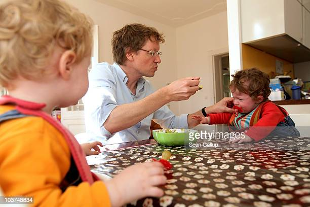 Oliver H. A married federal employee on 6-month paternity leave, feeds his twin 14-month-old daughters Alma and Lotte lunch at his home on August 31,...