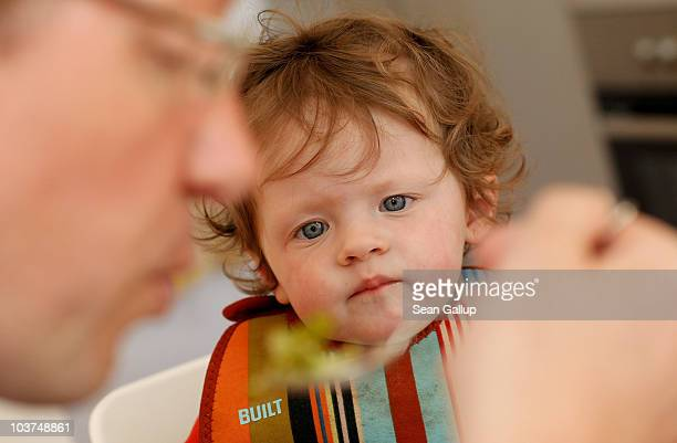 Oliver H. A married federal employee on 6-month paternity leave, feeds his twin 14-month-old daughter Lotte lunch at his home on August 31, 2010 in...