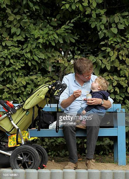 Oliver H. A married federal employee on 6-month paternity leave, feeds his twin 14-month-old daughter Alma a snack at a playground on August 31, 2010...