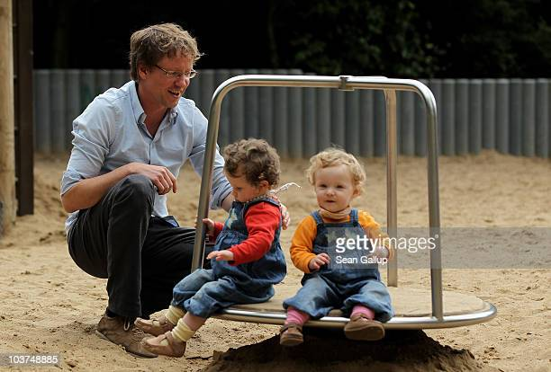 Oliver H. A married federal employee on 6-month paternity leave, plays with his twin 14-month-old daughters Lotte and Alma at a playground on August...
