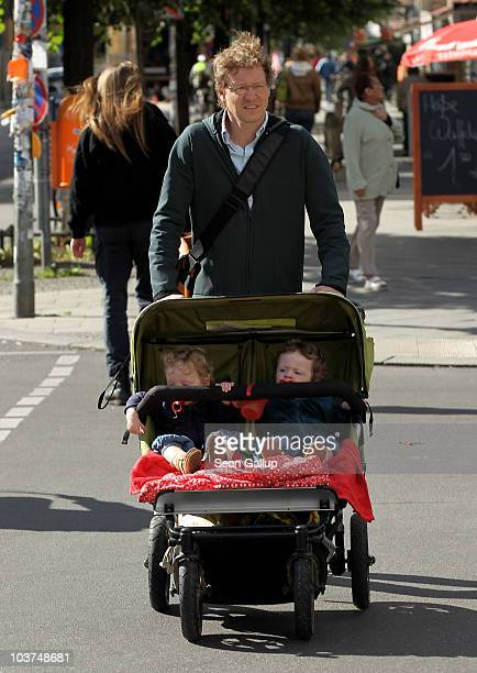 Oliver H. A married federal employee on 6-month paternity leave, pushes his twin 14-month-old daughters Lotte and Alma in a pram while doing errands...