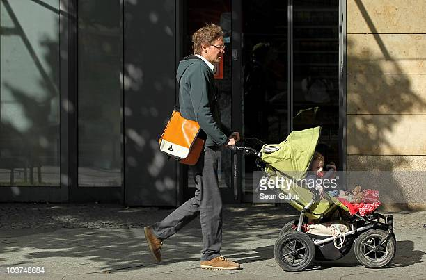 Oliver H a married federal employee on 6month paternity leave pushes his twin 14monthold daughters Lotte and Alma in a pram while doing errands near...