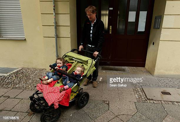 Oliver H. A married federal employee on 6-month paternity leave, pushes his twin 14-month-old daughters Lotte and Alma in a pram as he leaves his...