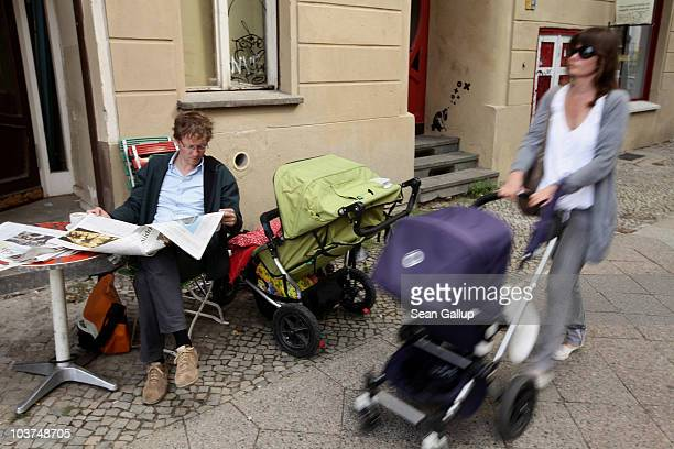 Oliver H. A married federal employee on 6-month paternity leave, reads a newspaper at an outdoor cafe while his twin 14-month-old daughters Lotte and...
