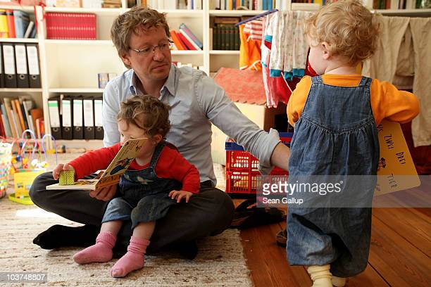 Oliver H. A married federal employee on 6-month paternity leave, reads to his twin 14-month-old daughters Alma and Lotte at his home on August 31,...