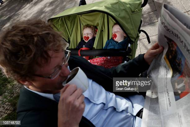 Oliver H. A married federal employee on 6-month paternity leave, sips coffee and reads a newspaper at an outdoor cafe while his twin 14-month-old...